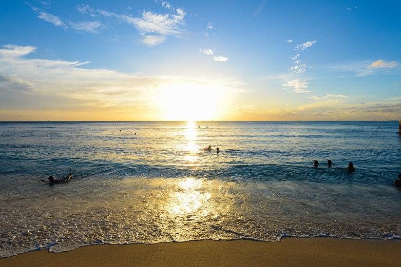 the sun over the ocean on Waikiki Beach